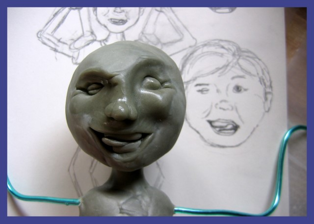 Sculpted face of boy sculpture next to sketch of the face