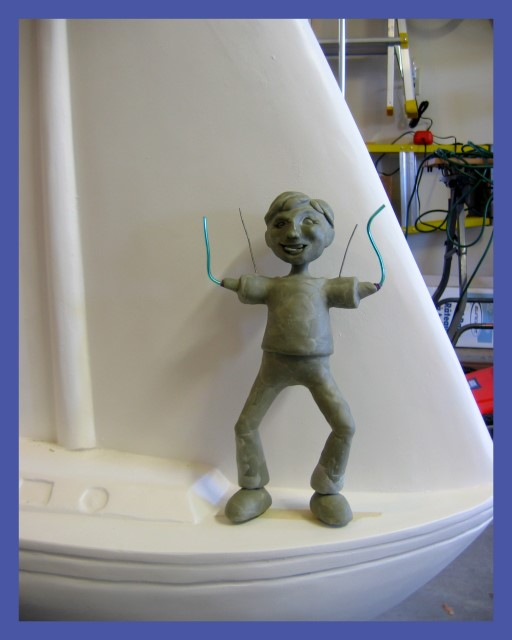 Boy sculpture on sailboat