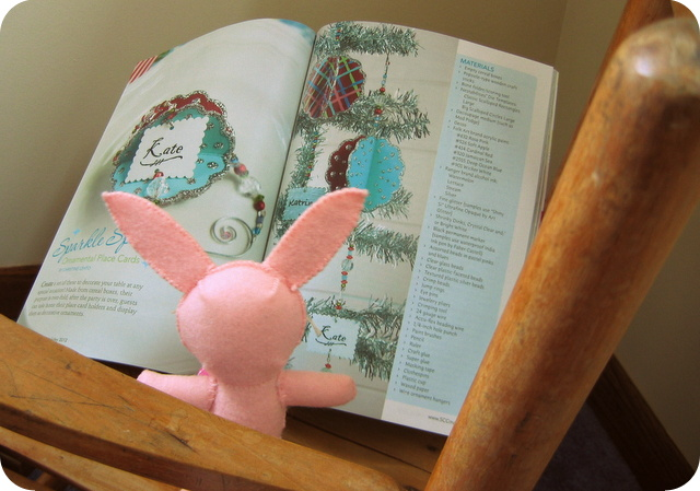 "Ralphie reading the ""Spakle ""Sphere"" glitter ornament article in Stitch Craft Create magazine"