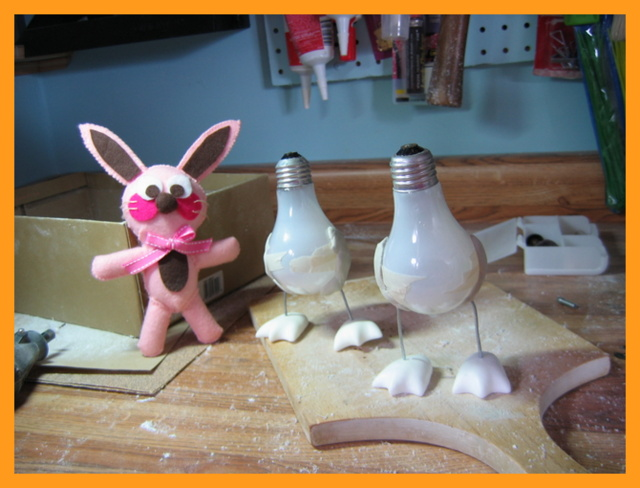 Ralphie the bunny next to work-in-progress light bulb penguin sculptures